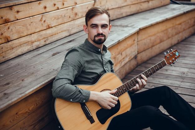 Jovem bonitão toca guitarra, pega um acorde, músico de rua Foto gratuita