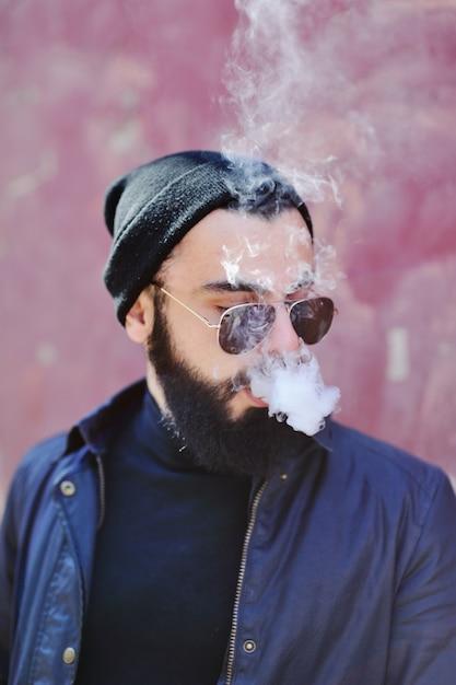 Jovem bonitinho com cigarro eletrônico Foto Premium