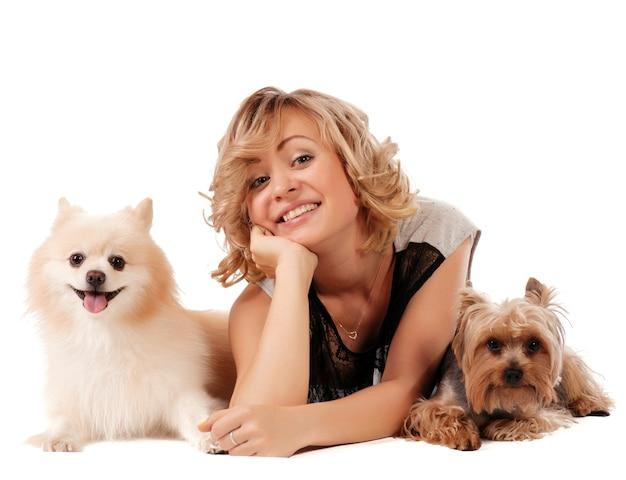 Jovem bonito abraçando seus cães enquanto está sentado isolado no branco - retrato Foto Premium