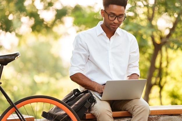 Jovem bonito africano usando computador portátil. Foto gratuita