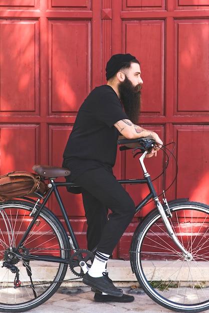 Jovem bonito andando de bicicleta ao ar livre em dia ensolarado Foto gratuita