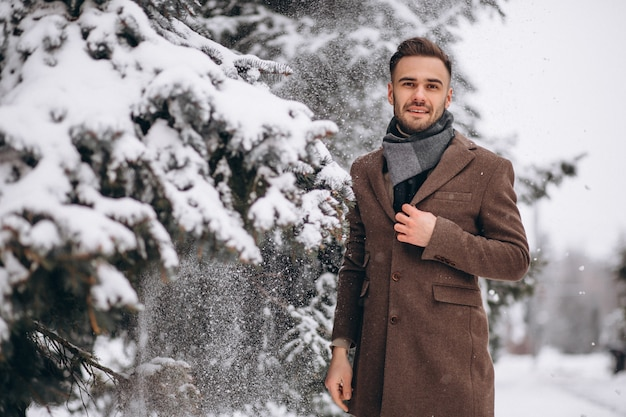 Jovem bonito andando em uma floresta de inverno Foto gratuita