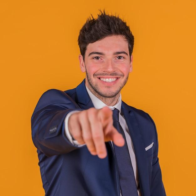 Jovem bonito apontando o dedo em direção a câmera contra um pano de fundo laranja Foto gratuita