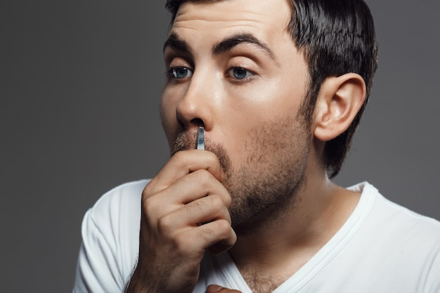 Jovem bonito, arrancando os cabelos no nariz ao longo da parede cinza Foto gratuita