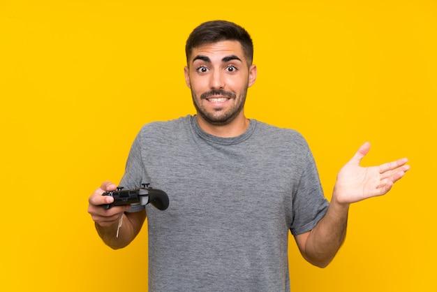 Jovem bonito brincando com um controlador de videogame sobre parede amarela isolada com expressão facial chocada Foto Premium