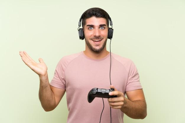 Jovem bonito brincando com um controlador de videogame sobre parede verde isolada com expressão facial chocada Foto Premium