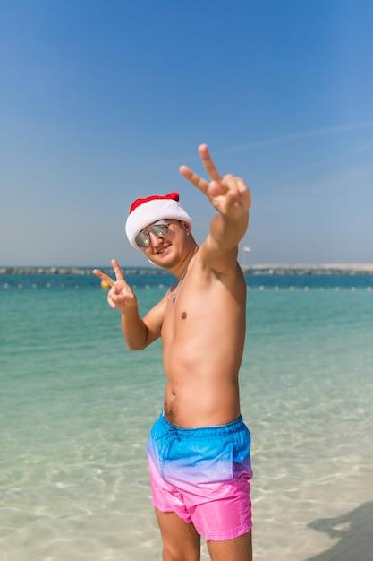 Jovem bonito chapéu de papai noel e óculos de sol com gesto de paz em pé no espaço da água do mar Foto Premium