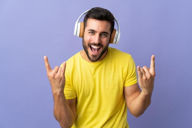 Jovem bonito com barba isolada na parede roxa, escutando música fazendo gesto de pedra Foto Premium