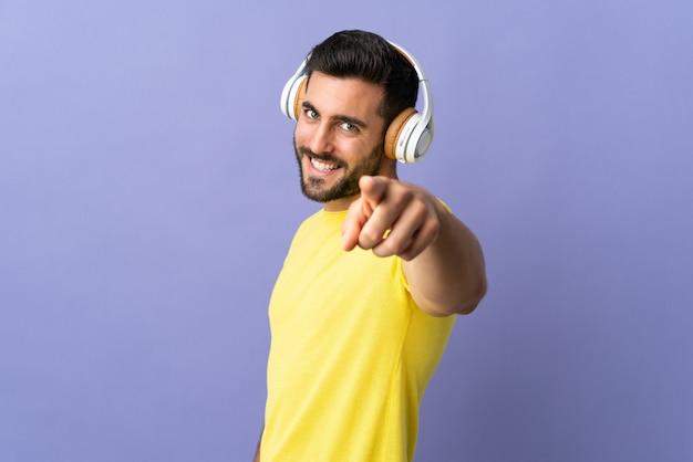 Jovem bonito com barba isolada na parede roxa, ouvindo música e apontando para a frente Foto Premium