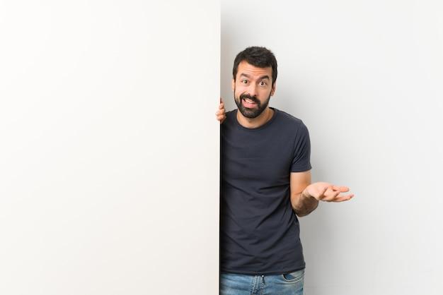 Jovem bonito com barba segurando um cartaz grande e vazio, fazendo o gesto de dúvidas Foto Premium