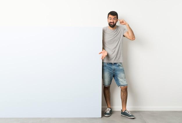 Jovem bonito com barba segurando um grande cartaz azul vazio, fazendo o gesto de loucura, colocando o dedo na cabeça Foto Premium