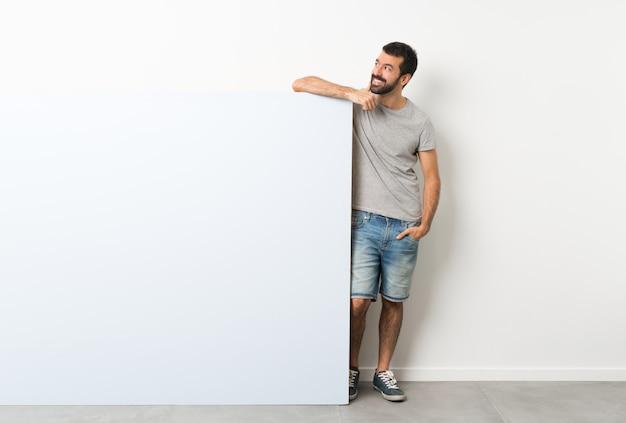 Jovem bonito com barba segurando um grande cartaz vazio azul pensando uma idéia enquanto olha para cima Foto Premium