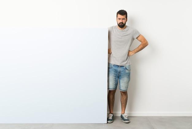 Jovem bonito com barba, segurando um grande cartaz vazio com raiva Foto Premium