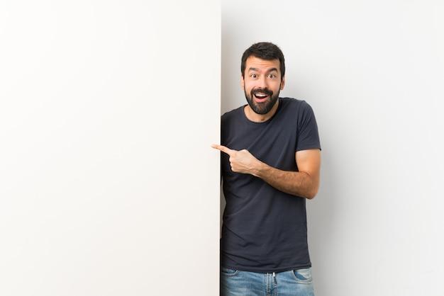 Jovem bonito com barba segurando um grande cartaz vazio surpreso e apontando o lado Foto Premium