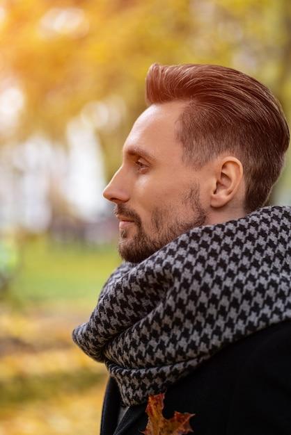 Jovem bonito com casaco azul escuro e lenço Foto Premium