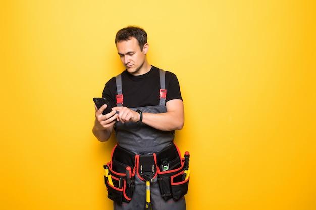 Jovem bonito com cinto de ferramentas usar telefone celular Foto Premium