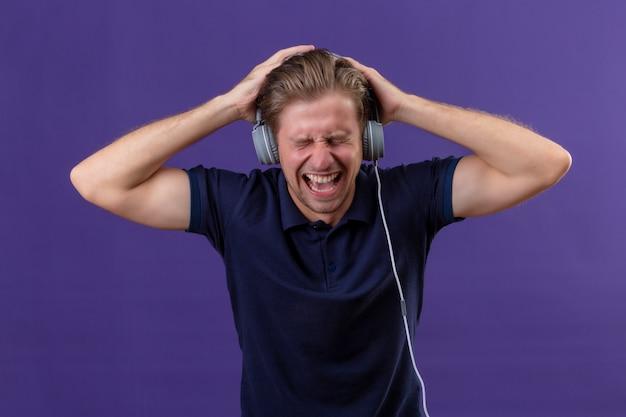 Jovem bonito com fones de ouvido grita enquanto ouve música com alto volume de pé sobre fundo roxo Foto gratuita
