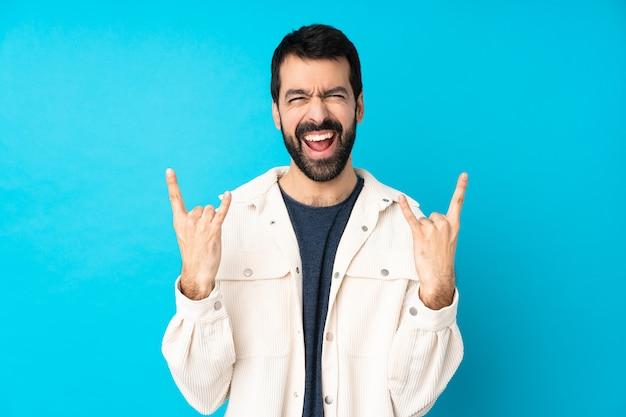 Jovem bonito com jaqueta de veludo branco sobre parede azul isolada, fazendo gesto de pedra Foto Premium