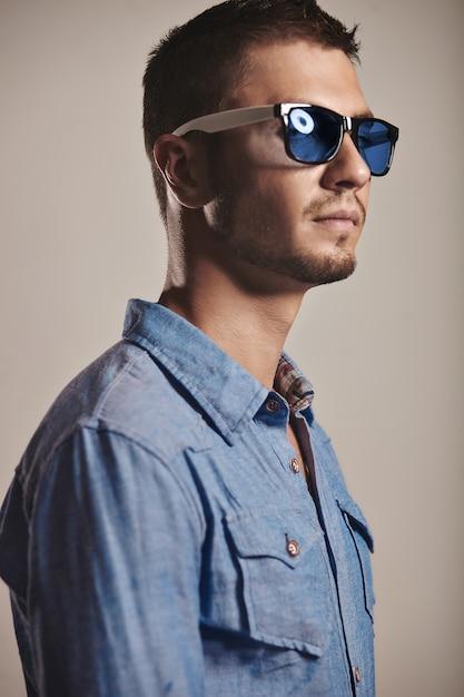 Jovem bonito com óculos de sol na moda em estúdio Foto gratuita