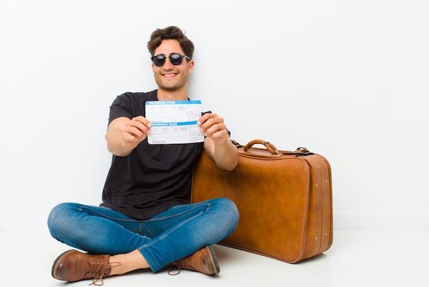 Jovem bonito com um bilhete de embarque, sentado no chão em uma sala branca Foto Premium