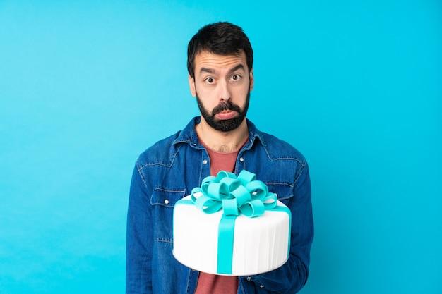 Jovem bonito com um bolo grande sobre parede azul isolada com expressão triste e deprimida Foto Premium