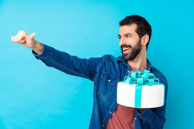 Jovem bonito com um bolo grande sobre parede azul isolada, dando um polegar para cima gesto Foto Premium