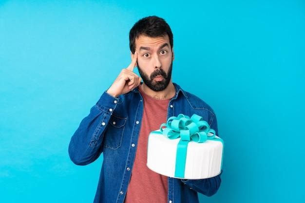 Jovem bonito com um bolo grande sobre parede azul isolada, pensando uma idéia Foto Premium