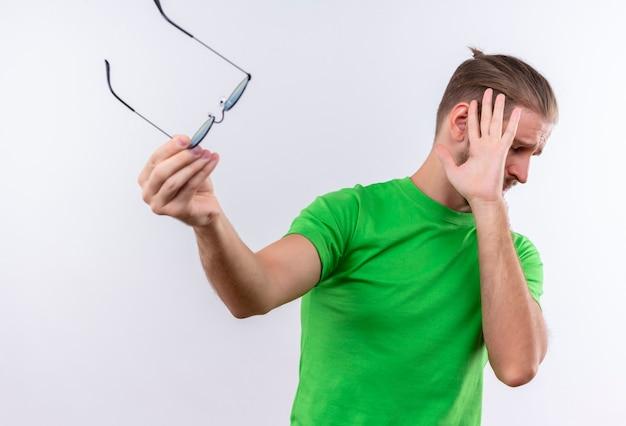 Jovem bonito com uma camiseta verde segurando os óculos e fazendo um gesto de defesa em pé sobre um fundo branco Foto gratuita