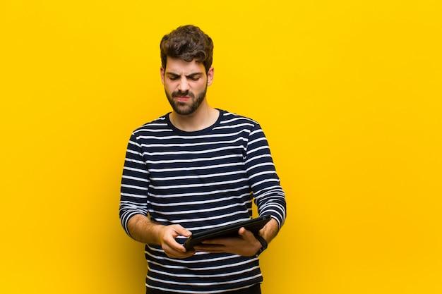 Jovem bonito contra fundo laranja Foto Premium