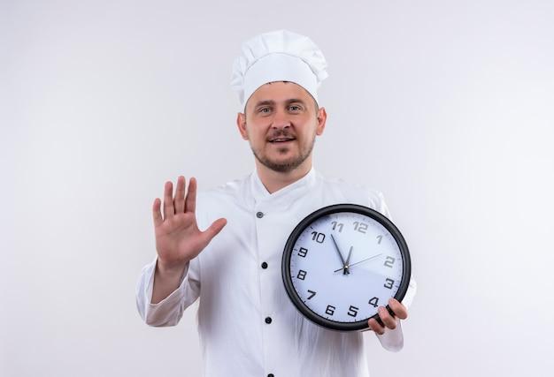 Jovem bonito cozinheiro sorridente com uniforme de chef segurando o relógio e levantando a mão, isolado no espaço em branco Foto gratuita