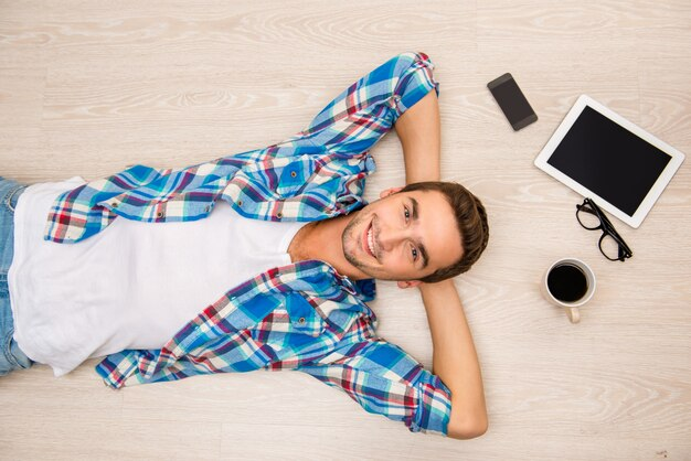 Jovem bonito deitado no chão de madeira na hora do almoço Foto Premium