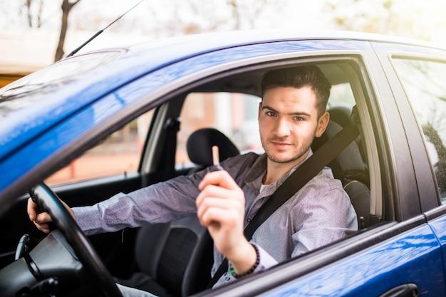 Jovem bonito dirigindo seu carro novo, segurando as chaves Foto gratuita