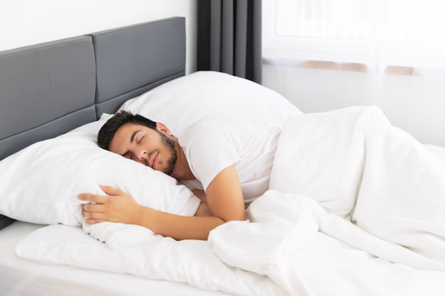 Jovem bonito dormindo em sua cama. Foto Premium