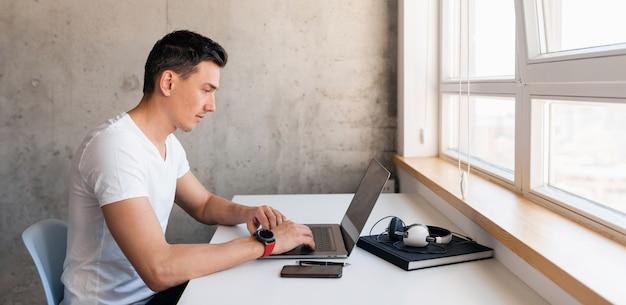 Jovem bonito e sorridente em roupa casual sentado à mesa trabalhando em um laptop e ficando em casa sozinho Foto gratuita