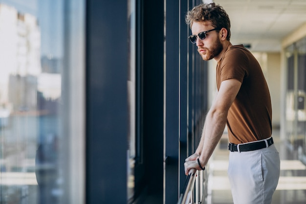 Jovem bonito em pé junto à janela no aeroporto Foto gratuita