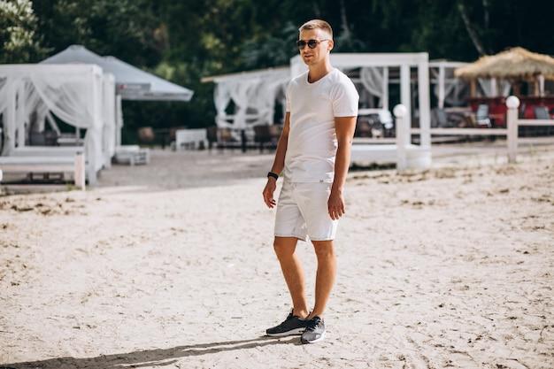 Jovem bonito em pé na praia pelo parque Foto gratuita