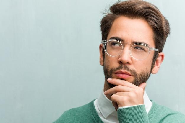 Jovem bonito empreendedor homem cara closeup duvidando e confuso, pensando em uma idéia ou preocupado com algo Foto Premium