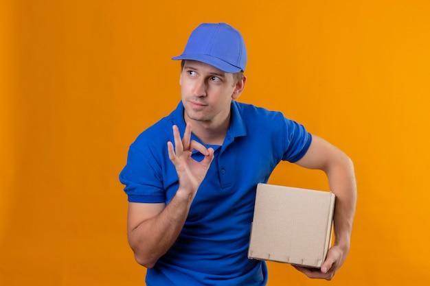 Jovem bonito entregador de uniforme azul e boné segurando um pacote olhando para o lado Foto gratuita