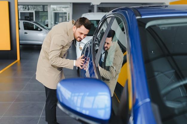Jovem bonito escolhendo um carro em um showroom de carros Foto Premium