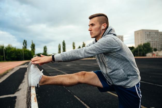 Jovem bonito fazendo exercícios, trabalhando fora as pernas, ouvindo música Foto gratuita