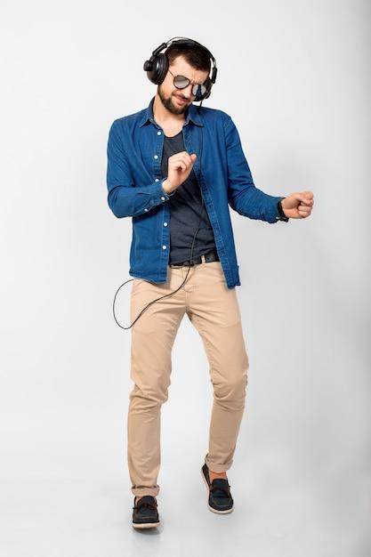 Jovem bonito feliz e sorridente dançando e ouvindo música em fones de ouvido isolados no fundo branco do estúdio, vestindo camisa jeans e óculos escuros Foto gratuita