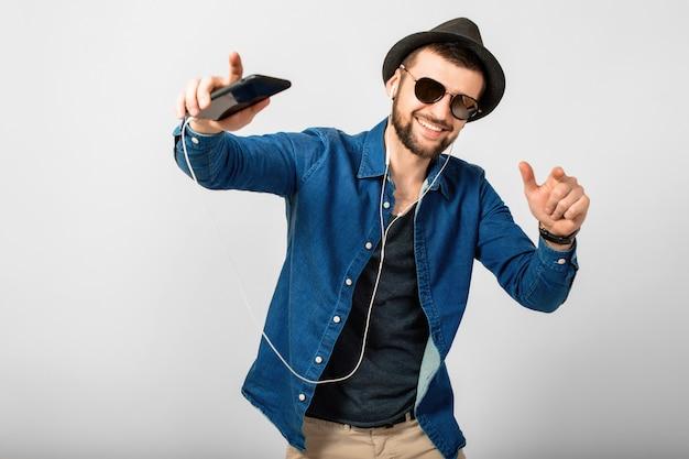 Jovem bonito feliz e sorridente ouvindo música em fones de ouvido isolados no fundo branco do estúdio, segurando o smartphone, vestindo camisa jeans, chapéu e óculos escuros Foto gratuita