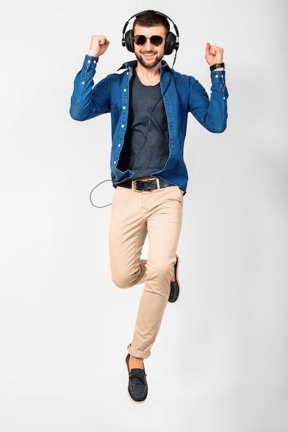Jovem bonito feliz sorridente dançando e ouvindo música em fones de ouvido isolados no fundo branco do estúdio, vestindo camisa jeans e óculos escuros. o vencedor pulando com sucesso Foto gratuita
