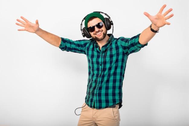 Jovem bonito feliz sorridente ouvindo música em fones de ouvido isolados no fundo branco do estúdio, vestindo camiseta e óculos escuros Foto gratuita