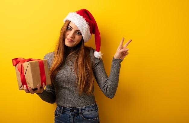 Jovem, bonito, mulher segura, presente, fazendo um gesto, de, vitória Foto Premium