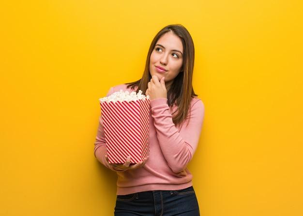Jovem bonito mulher segurando um balde de pipoca, duvidando e confuso Foto Premium