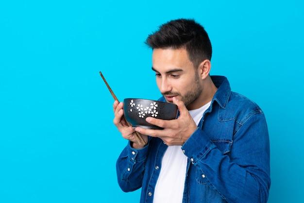 Jovem bonito muro azul isolado, segurando uma tigela de macarrão com pauzinhos e comê-lo Foto Premium