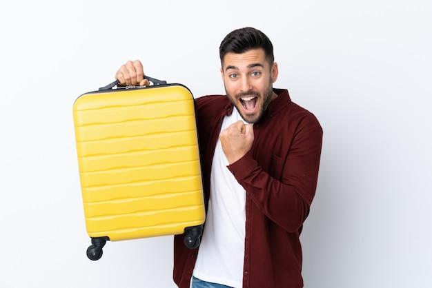 Jovem bonito muro branco isolado em férias com mala de viagem Foto Premium