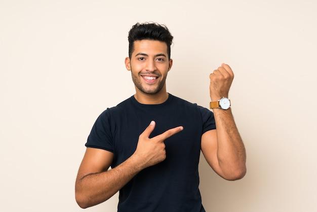 Jovem bonito muro isolado mostrando o relógio de mão Foto Premium