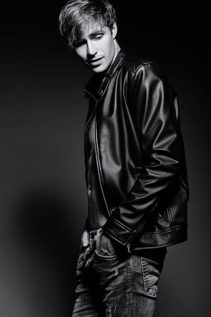 Jovem bonito musculoso cabe homem modelo masculino na jaqueta de couro posando no estúdio, mostrando seus músculos abdominais Foto gratuita